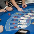 Image of men and women gambling playing blackjack cards - Stock Photo