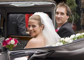 Bride and groom arrive at reception in vintage wedding car — Stock Photo