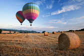 Hot air balloons over hay bales sunset landscape — Stock Photo