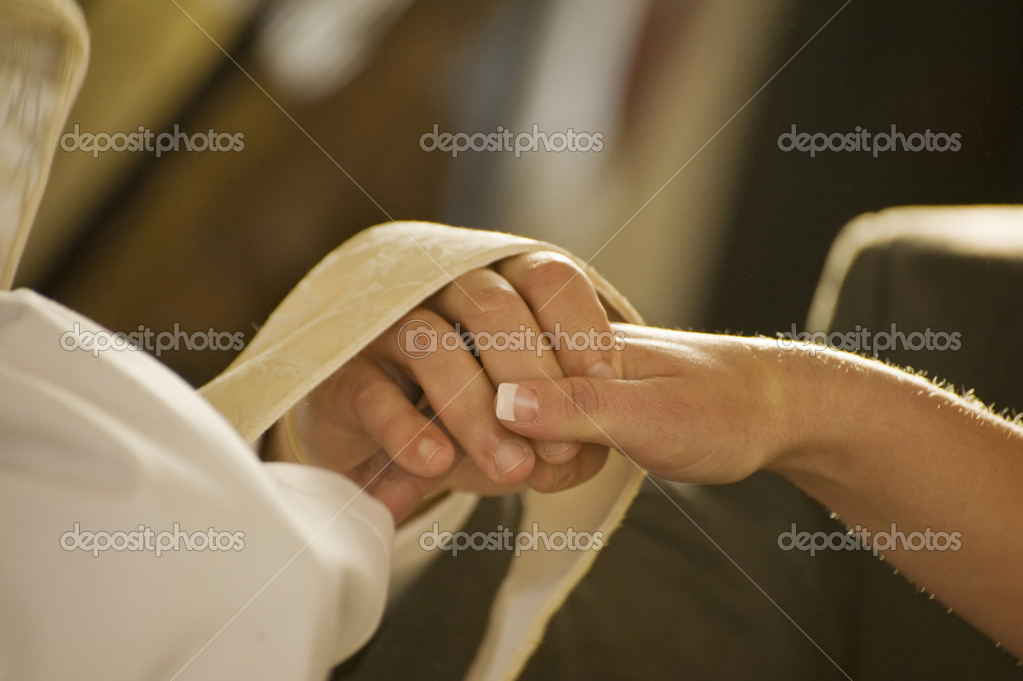 Close up of bride and groom having rings blessed during real wedding ceremony — Stock Photo #7128145