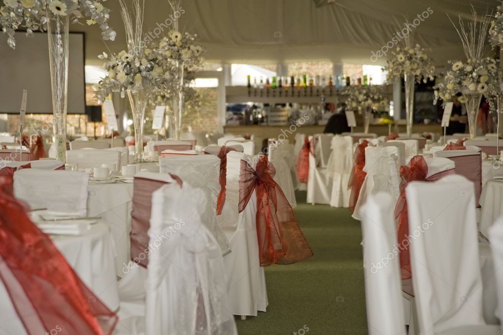 Wide shot of wedding reception awaiting guests and bride and groom with red
