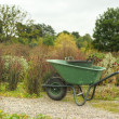 Garedning scene with wheelbarrow in country garden - Stock Photo