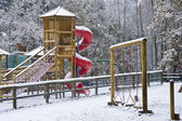 Empty children's playground in snow — Stock Photo