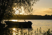 Fishing boat on calm lake during vibrant Summer sunset — Stock Photo