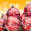 Red Christmas bauble decorations on warm golden background — Stock Photo