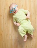 Mały chłopiec w zabawa zabawka okulary leży na podłodze — Zdjęcie stockowe
