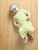 Little boy in fun toy spectacles lies on the floor — Stock Photo