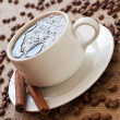 Cup of coffee and coffee beans on sacking material — Stock Photo