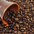 Coffee beans falling from a coffee cup — Stock Photo