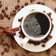 Cup of coffee and coffee beans on sacking material — Stock Photo #6844561
