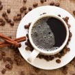 Stock Photo: Cup of coffee and coffee beans on sacking material