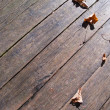 Autumn leaves over wooden boards floor — Lizenzfreies Foto