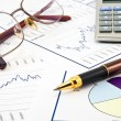 Stock Photo: Business background, financial data concept with pen and glasse