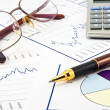 Business background, financial data concept with pen and glasse — Stock Photo #7727174