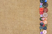 Old colorful buttons on the background burlap — Stock Photo