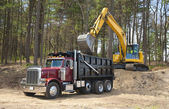 Dump truck and excavator — Stock Photo