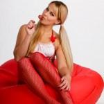 Pretty girl on pouf with lollipop — Stock Photo #7018767