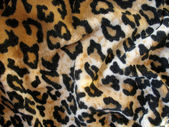Fleecy brown leopard skin fabric background — Stock Photo