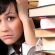 Young student girl holding her head behind a lot of books — Stock Photo #7123446