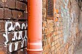Sewage pipe on brick abandoned wall — Stock Photo