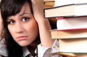 Young student girl holding her head behind a lot of books — Stock Photo