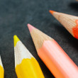 Colorful pencils on dark background lined up — Stock Photo #7786257
