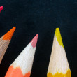 Colorful pencils on dark background lined up — Stock Photo