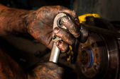 Hard working man with hands full of oil — Stock Photo