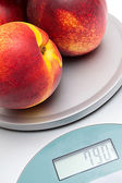 Peaches on the scales on a white background — Stock Photo