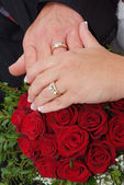 Wedding rings and roses bouquet — Stock fotografie
