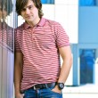 Foto Stock: Portait of a young man standing with his hands in pocket