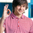 Happy young man indicating OK sign against the window — Stock Photo