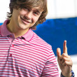 Closeup of smiling young man pointing up — Stock Photo #6883397