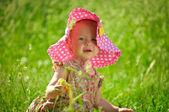 Słodkie maleństwo siedzi w trawie — Zdjęcie stockowe
