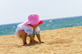 Baby playing on the beach — Stockfoto