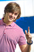 Closeup of smiling young man pointing up — Stock Photo