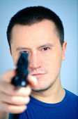 Young man holding a pistol — Stock Photo