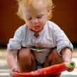 Infant baby with a melon — Stockfoto
