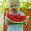 Infant baby with a melon — Stock Photo