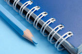 Blue pencil and spiral of notebook — Stock Photo