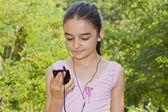 Chica escuchando música en un smartphone — Foto de Stock