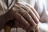 Hand of a senior man with a cane — Stock Photo