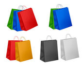 Ssorted colored shopping bags including red, yellow, blue and pink on a whi — Stock Vector