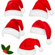 Collection of red santa hats with and Christmas holly. Vector. — Vecteur