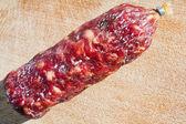 Italian salami on wooden board — Stock Photo