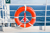 Red life buoy on side of cruise liner — Stock Photo