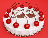Celebration: cake with cherries on red — Stock Photo