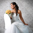 Stock Photo: BRIDE LOOKING AT BOUQUET