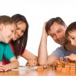 Happy family playing at table - Stock Photo