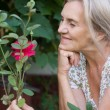 Aged woman with flower — Stock Photo #6784586